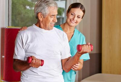 nurse helping a senior man exercising